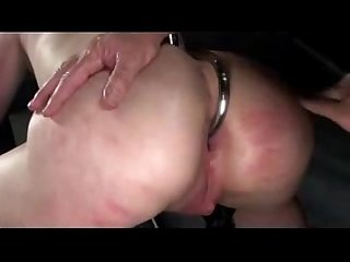 Bondaged busty girl with legs up whipped fisted fucked swallowing cum in the dungeon