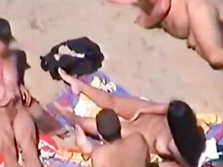 Two guys cums on nude girl at the beach