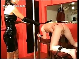 Latex wearing dominatrix with big tits hits slave on his with a whip and puts a finger up his