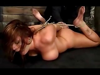 Busty hogtied girl getting her pussy fingered on the floor in the dungeon