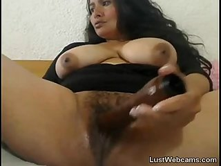 Brunette milf fingers her hairy pussy on cam
