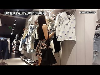 Beautiful young woman in mini skirt caught in the clothes store
