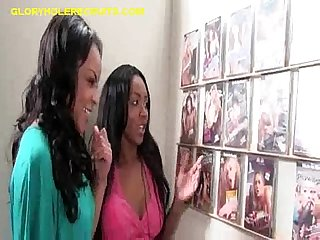 Two black babes suck white cock through gloryhole