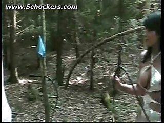 Brunette mistress hits slave tied to tree with a whip on his back bdsm